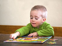 Bambino che lavora ad un puzzle. Fotografie Stock Libere da Diritti
