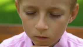 Bambino maschio turbato che si siede da solo sul banco in parco, concetto d'oppressione, infanzia archivi video