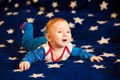Bambino 6 mesi e sorridere a casa su una coperta blu del cielo stellato Fotografia Stock Libera da Diritti