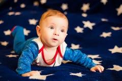 Bambino 6 mesi e sorridere a casa su una coperta blu del cielo stellato Immagini Stock