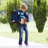 Bambino messo a fuoco serio con i libri preoccupantesi dello zaino in sue mani esterno Immagini Stock