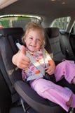 Bambino messo nella sede del bambino nell'automobile Immagine Stock