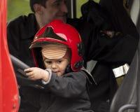 Bambino nel casco di un vigile del fuoco nel camion dei vigili del fuoco Fotografia Stock Libera da Diritti