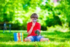 Bambino nel cortile della scuola con la lente d'ingrandimento Fotografie Stock Libere da Diritti