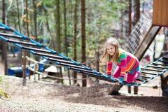 Bambino nel parco di avventura Bambini che scalano la traccia della corda Fotografie Stock Libere da Diritti