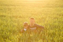 Bambino nel prato nell'erba alta al tramonto Fotografie Stock Libere da Diritti