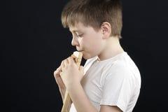 Bambino nel sideview di gioco bianco del panflute Immagine Stock