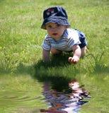 Bambino nell'erba dall'Water Fotografie Stock