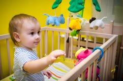 Bambino nella greppia che gioca con i giocattoli fotografia stock