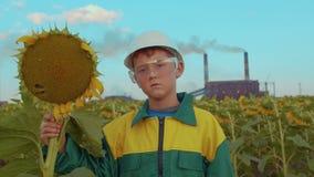 Bambino nella maschera protettiva con il girasole della pianta sull'impianto industriale del fondo Inquinamento ambientale stock footage