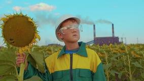 Bambino nella maschera protettiva con il girasole della pianta sull'impianto industriale del fondo Inquinamento ambientale archivi video