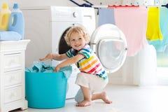 Bambino nella stanza di lavanderia con la lavatrice immagine stock libera da diritti