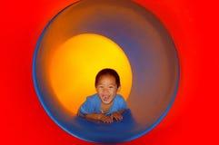 Bambino nella trasparenza del tubo Fotografia Stock
