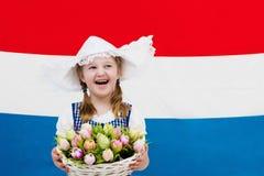 Bambino olandese con i fiori del tulipano e la bandiera olandese Fotografia Stock