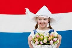 Bambino olandese con i fiori del tulipano e la bandiera olandese Fotografie Stock Libere da Diritti