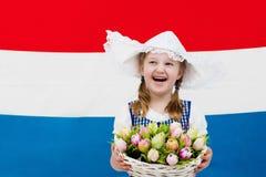 Bambino olandese con i fiori del tulipano e la bandiera olandese Immagine Stock Libera da Diritti