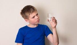 Bambino osservando un bicchiere d'acqua pieno a metà o vuoto a metà immagini stock