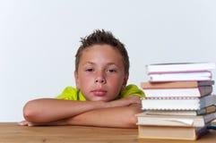 Bambino pensieroso del Tween che si siede alla tavola con i libri Fotografia Stock Libera da Diritti