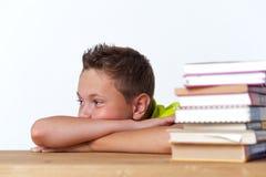 Bambino pensieroso del Tween che si siede alla tavola con i libri Immagine Stock