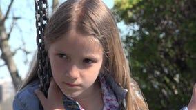 Bambino pensieroso triste nell'oscillazione, ragazza infelice che gioca da solo bambino all'aperto e depresso video d archivio