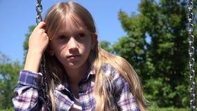 Bambino pensieroso triste nell'oscillazione, ragazza infelice che gioca da solo bambino all'aperto e depresso 4K video d archivio