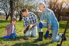 A bambino più anziano dei membri della famiglia insegnando a come preoccuparsi per la natura fotografie stock