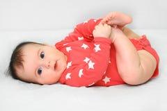 Bambino piacevole che gioca con i suoi piedi Fotografie Stock