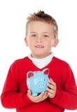 Bambino piacevole con il salvadanaio blu Immagine Stock