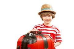 Bambino piacevole con una valigia rossa Fotografie Stock Libere da Diritti