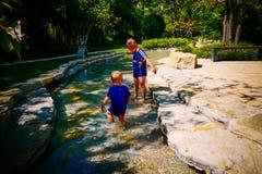 Bambino piccolo che gioca fuori nel fiume immagine stock