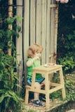 Bambino piccolo che mangia vicino al cespuglio di rose Fotografia Stock Libera da Diritti