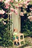 Bambino piccolo che mangia vicino al cespuglio di rose Fotografia Stock
