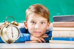 Bambino piccolo che si siede con la sveglia vicino alla lavagna Immagine Stock