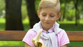 Bambino piccolo che si siede sul banco e che mangia banana durante la pausa della scuola, spuntino sano stock footage