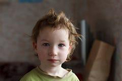 Bambino piccolo che si siede vicino alla finestra e che pensa a qualcosa Ha bei grandi capelli Bambino sveglio Fotografia Stock Libera da Diritti