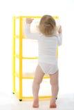 Bambino a piedi nudi con un what-not isolato su bianco Fotografie Stock