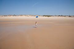 Bambino posteriore che corre alla spiaggia del parasole Immagine Stock