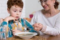 Bambino povero del mangiatore durante il pranzo Immagine Stock