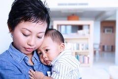 Bambino preoccupantesi di professione d'infermiera della madre a casa Fotografie Stock Libere da Diritti