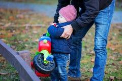 Bambino prescolare con il padre divertendosi con il triciclo all'aperto fotografie stock