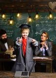 Bambino pronto per il banco Ragazzino in grandi cappotto del vestito e cappuccio di graduazione Allievo con la madre ed il padre  Fotografia Stock