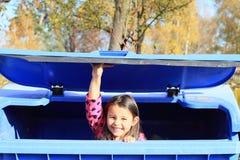 Bambino - ragazza che si nasconde in un contenitore Fotografia Stock