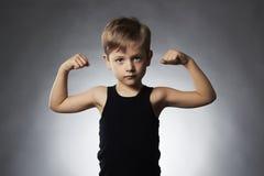 Bambino Ragazzino divertente Metta in mostra il ragazzo bello che mostra i suoi muscoli del bicipite della mano fotografia stock libera da diritti
