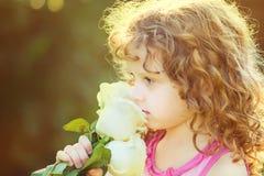 Bambino riccio con i fiori in sua mano Tonalità della foto Fil di Instagram immagine stock