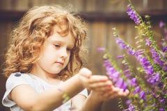 Bambino riccio con i fiori in sua mano Tonalità della foto Fil di Instagram fotografie stock