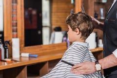bambino riccio piccolo coperto di tessuto rigato che si siede al parrucchiere mentre taglio del barbiere immagine stock