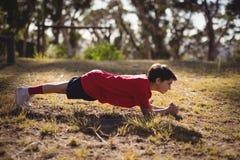 Bambino risoluto che si esercita durante la corsa ad ostacoli fotografia stock
