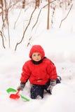 Bambino in rivestimento rosso che si siede sulla neve Fotografia Stock