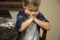 Bambino scontroso dopo avere contribuito a cuocere Immagine Stock