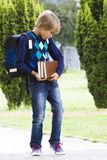 Bambino serio con i libri preoccupantesi dello zaino in sue mani esterno Fotografie Stock